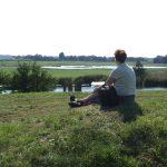 Zittende vrouw kijkt uit over waterlinielandschap